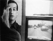A mirror reflects the face of a man with his back to the viewer. Hand raised and lips parted, he is making up his right eye. Next to him, a television shows footage of a highway shot from a moving car.