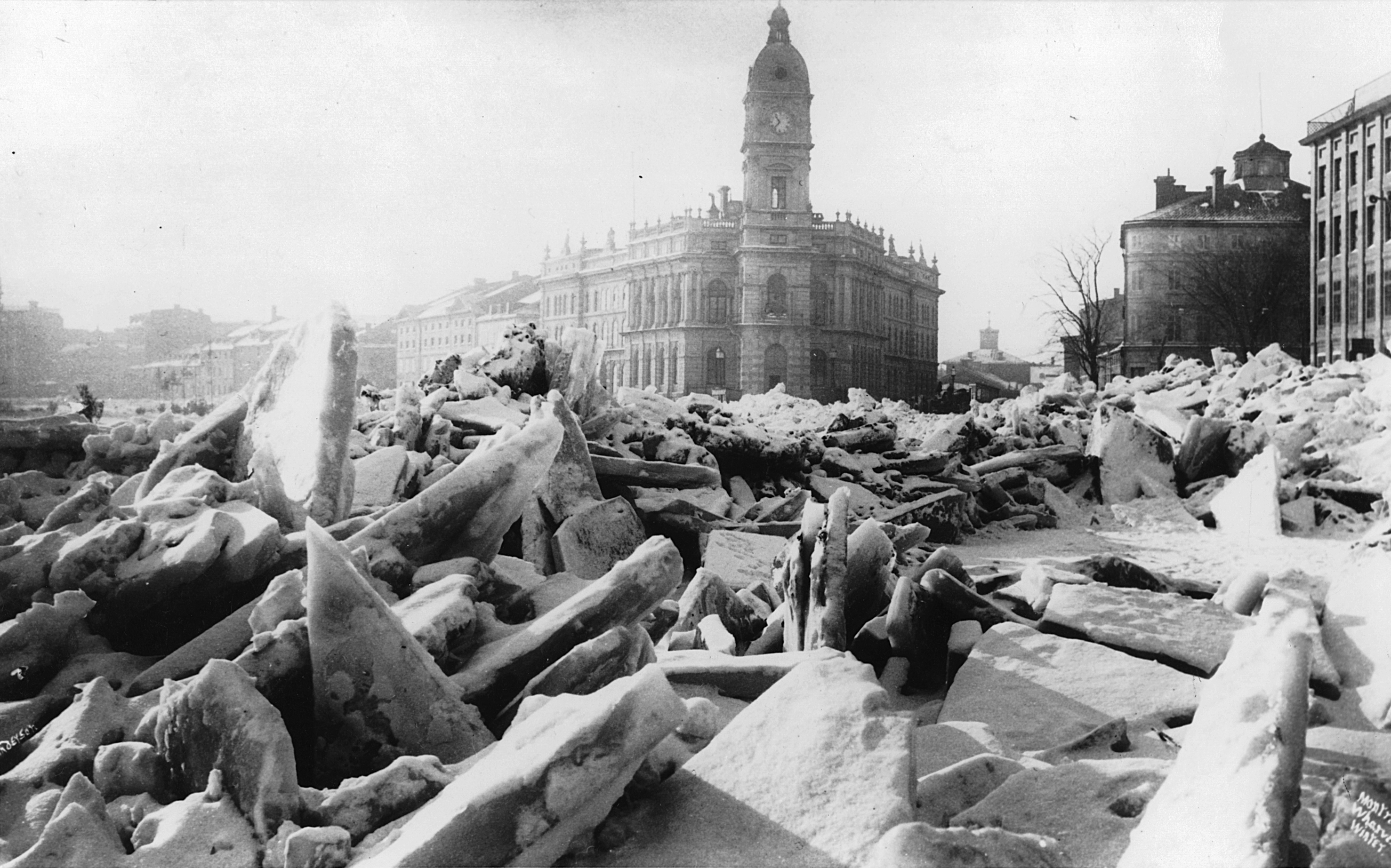 This black-and-white photograph shows a jumbled heap of ice slabs in the foreground. Buildings in Montréal's harbour appear in the background.