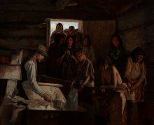 Copper-skinned people wait in line in the doorway of a gloomy cabin. Seated at the left of the composition, a white man is measuring out a ration of flour.