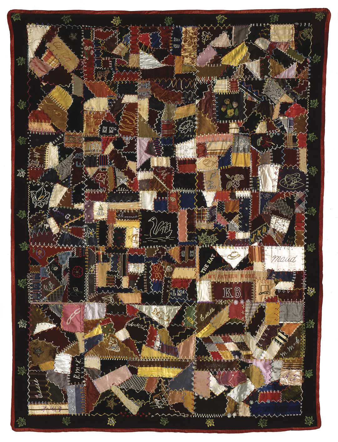 This rectangular coverlet is made of irregular pieces of fabric stitched together with white and coloured thread using traditional quilting techniques. It is embroidered with various motifs (swan, flowers, maple leaves) and names.