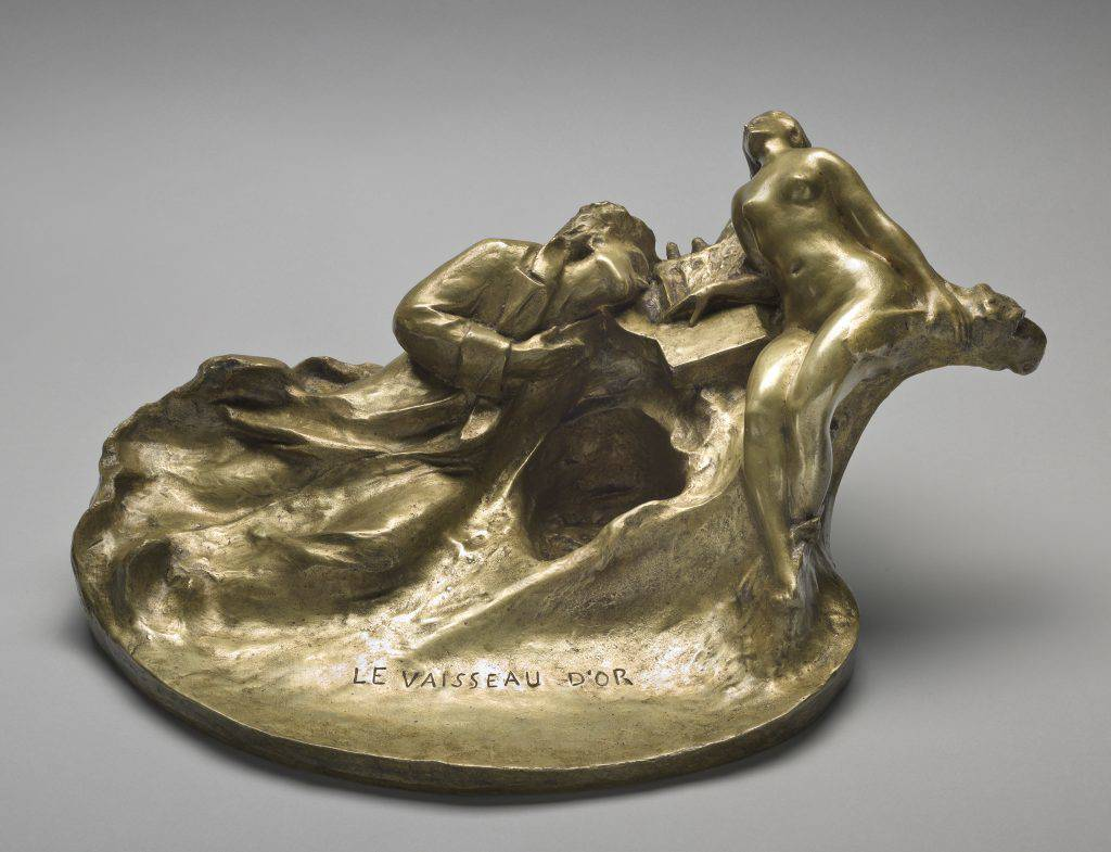 This small gilt-bronze decorative object depicts a reclining man leaning on a lyre. Near him lies a nude woman with her head thrown back. Between them is a hollow designed to hold ink.
