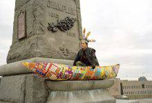 This colour photograph shows the base of a monument with Champlain's name carved in relief. A canoe made of cereal boxes is perched on a ledge, and the man sitting in it wears a headdress made of the same material.