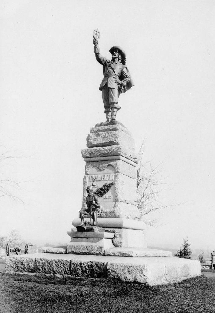 This black-and-white photograph shows a monument topped by a sculpture of a man in 17th-century attire holding an astrolabe. On the base of the monument is a much smaller sculpture of a crouching Aboriginal scout.