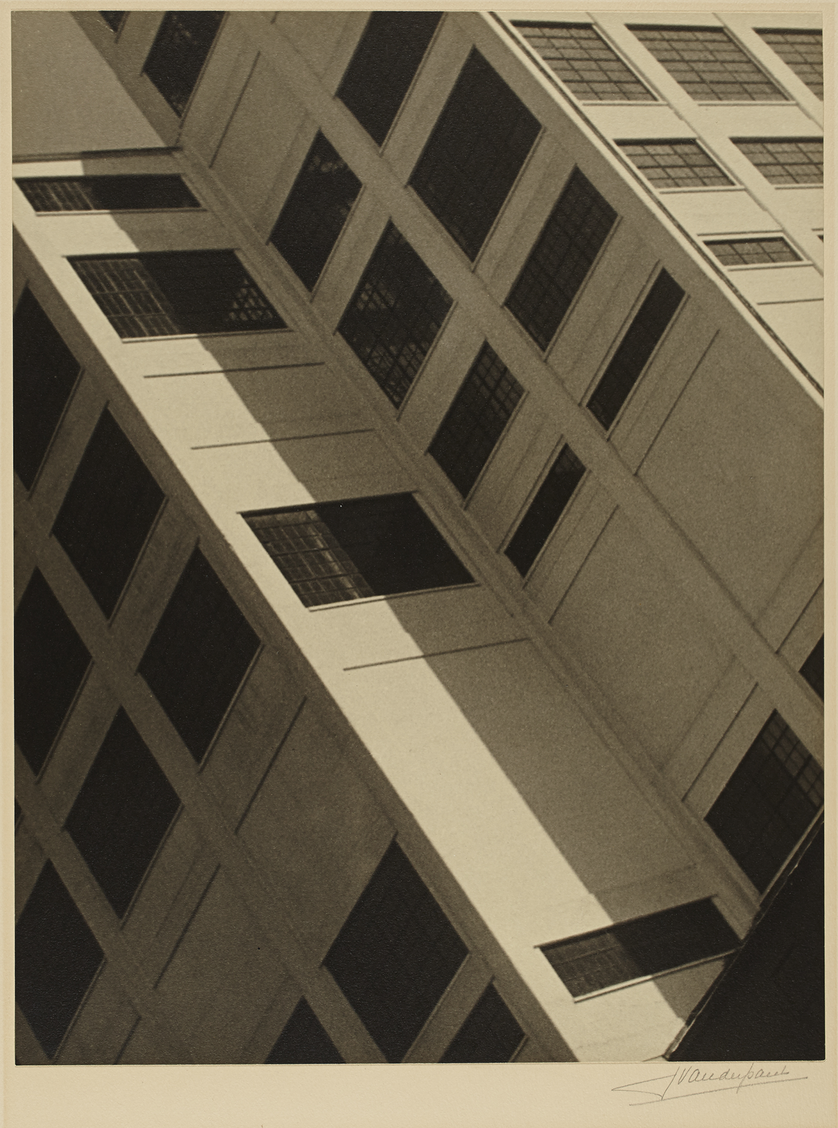This black-and-white photograph presents an oblique view of a multistory building with large dark windows. The tight framing reveals only part of the architecture, whose structure occupies the entire surface of the image.