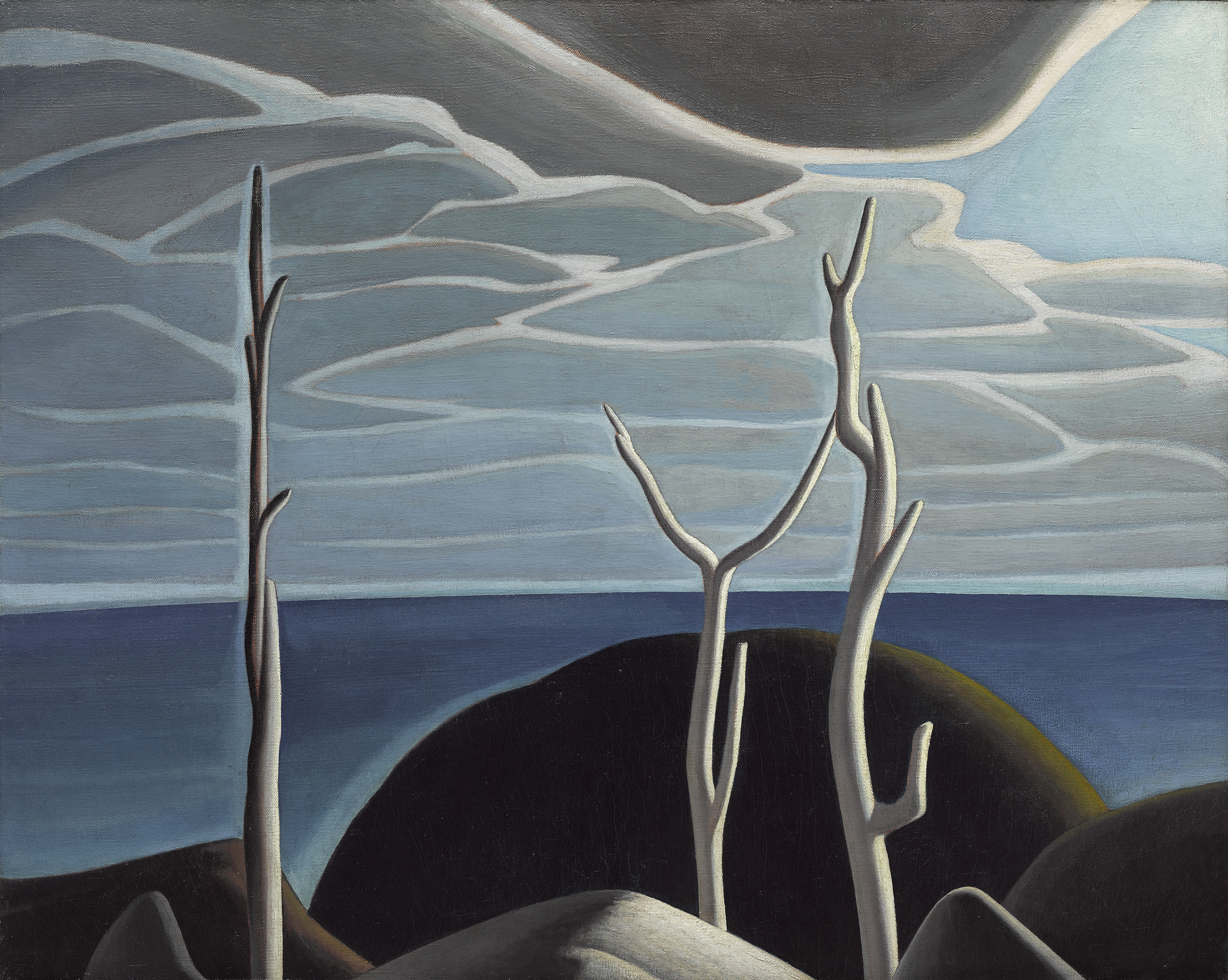 In the foreground of this painting, three dead trees stand erect in front of brownish rocky masses. Beyond, the horizon line separates the blue sky layered in white and grey clouds from the smooth surface of the darker blue lake.
