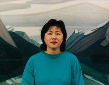 This photograph shows a woman looking at the camera. Behind her is a painting of a mountain partially covered in snow.