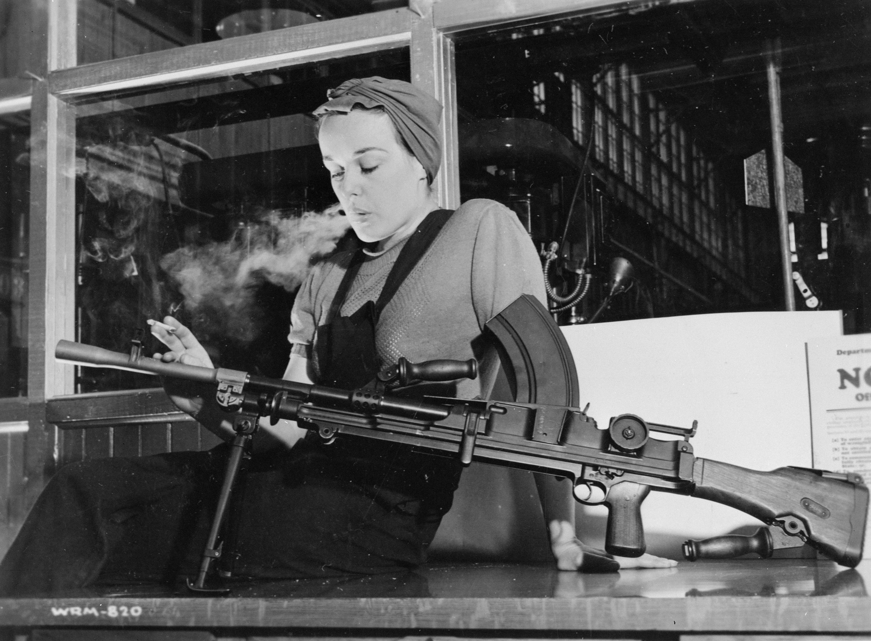 This black-and-white photograph shows a woman in overalls with her hair wrapped in a kerchief. Seated on a table, she is smoking a cigarette while gazing at a Bren machine gun. A factory building is visible through the window behind her.