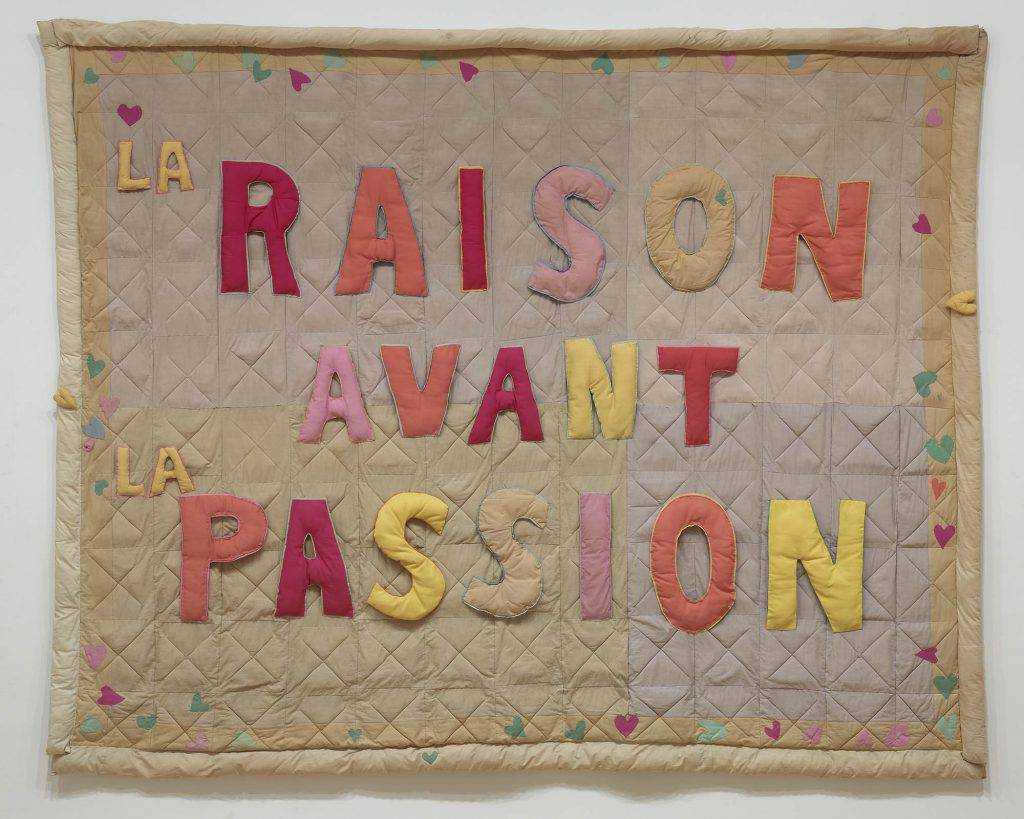 "This rectangular textile work is made of pieces of fabric stitched together like a quilt. Against the checkered background, brightly coloured letters spell out the French words ""La raison avant la passion."""