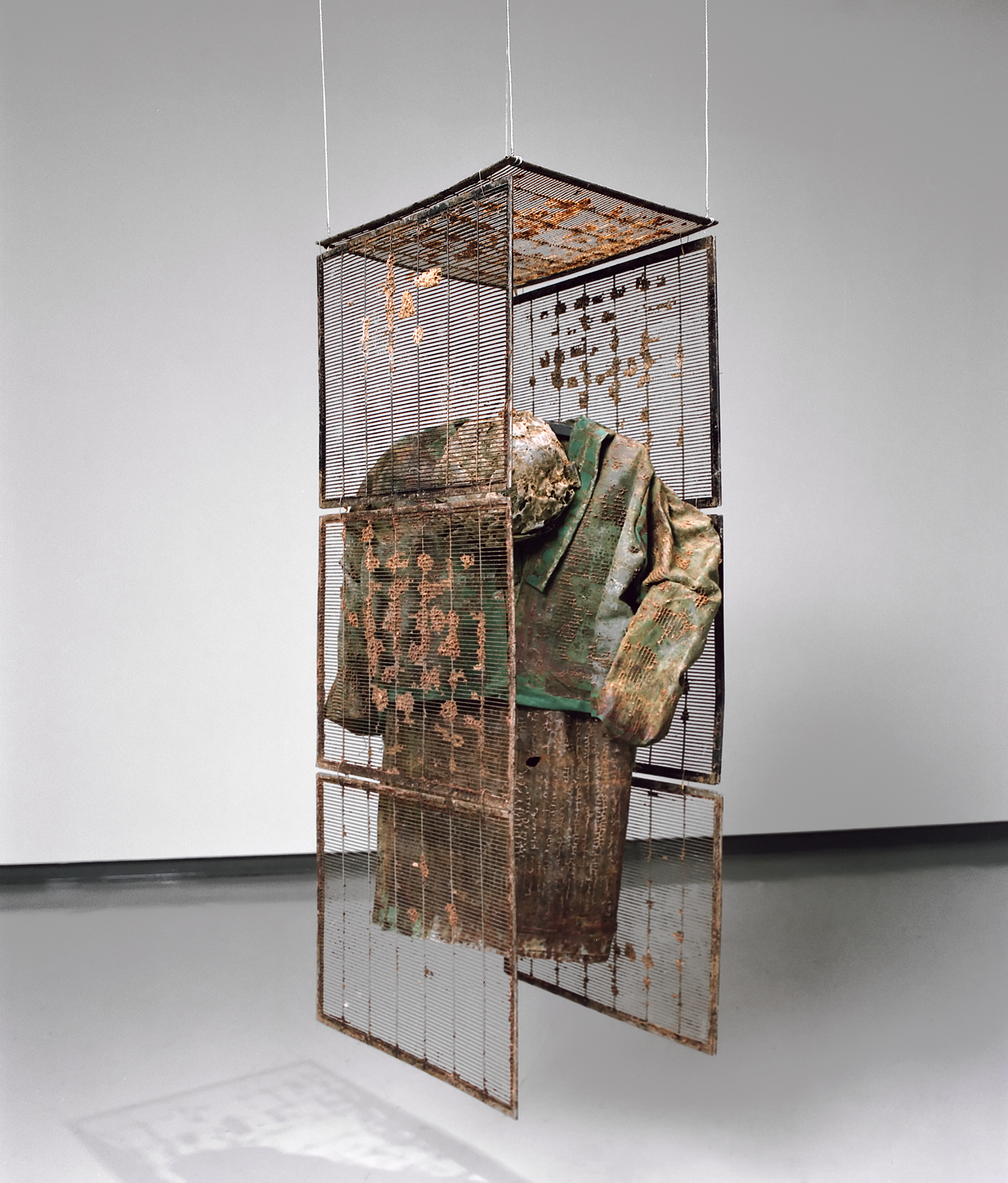 This structure composed of wire-mesh screens is suspended from the ceiling. Inside it hang a jacketed dress and a hat encrusted with beeswax.