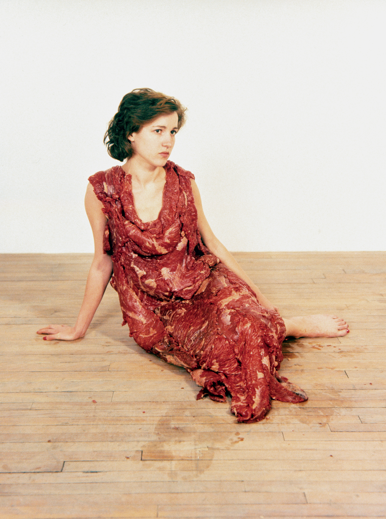 This photograph shows a dress made of slabs of raw beef stitched together hangs on a woman.