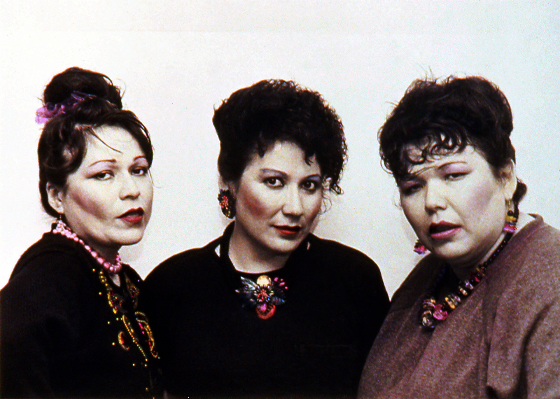 This hand-coloured, high-contrast black-and-white photo shows three women bust-length, facing the camera. Their hair is done up and they are wearing showy makeup. The background is neutral white.