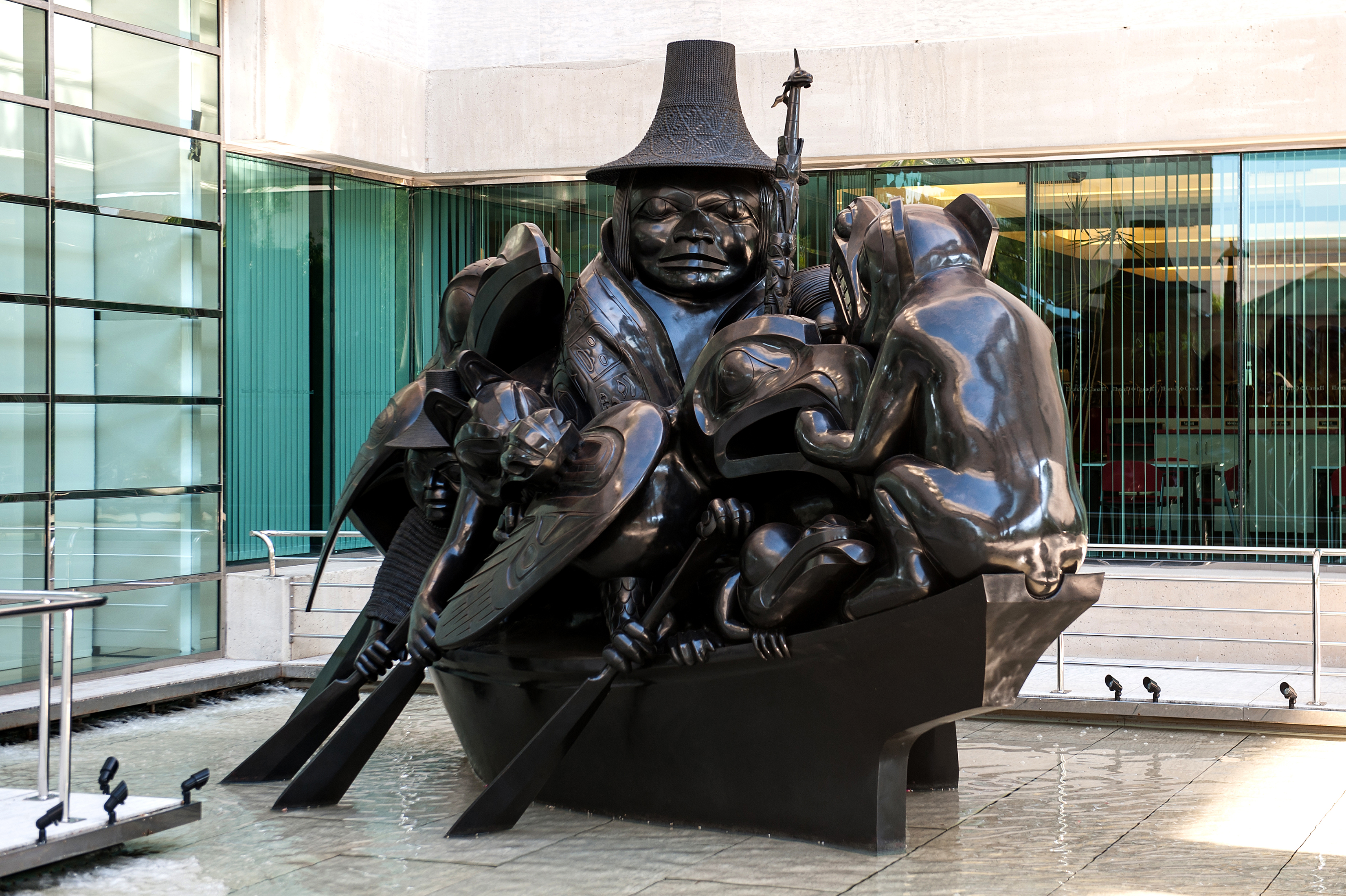 This black-patinated bronze sculpture represents a canoe crowded with thirteen figures. The angled photo shows seven of them: a raven, two men, a wolf, an eagle, a frog and a bear. The sculpture sits in a shallow pool.