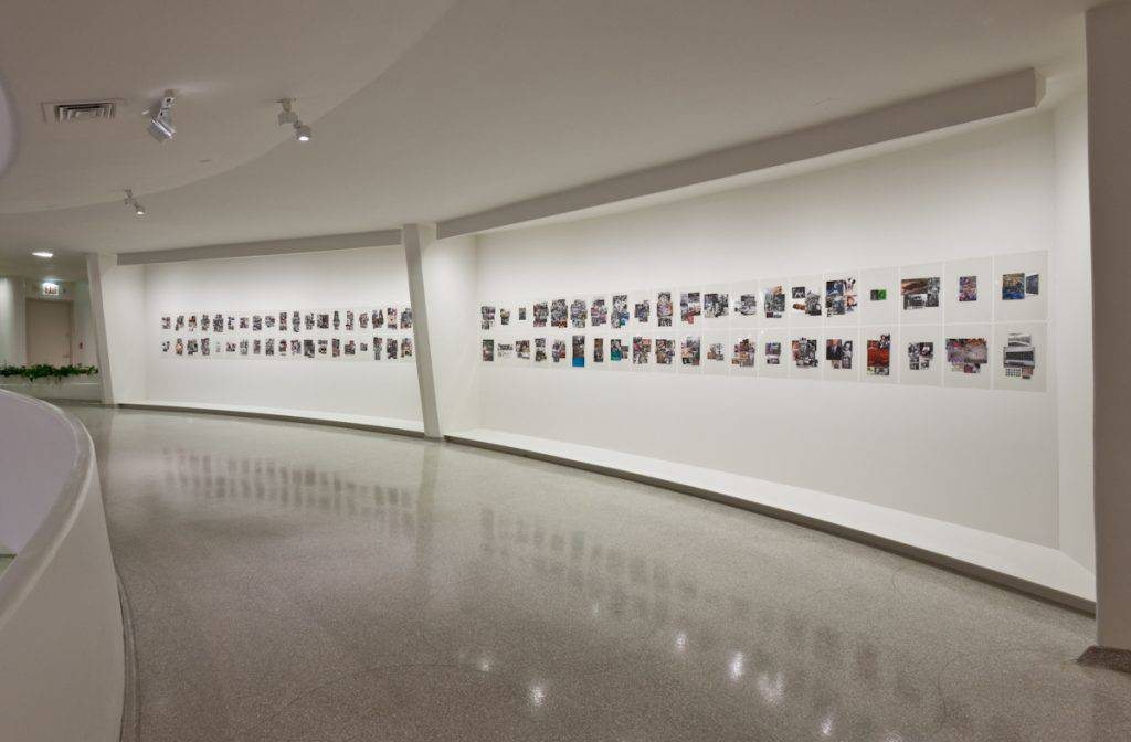 On a curved, white wall of a museum, 84 transparent panels hang in two tiers. Each panel contains one or more photographs taken from various print sources.