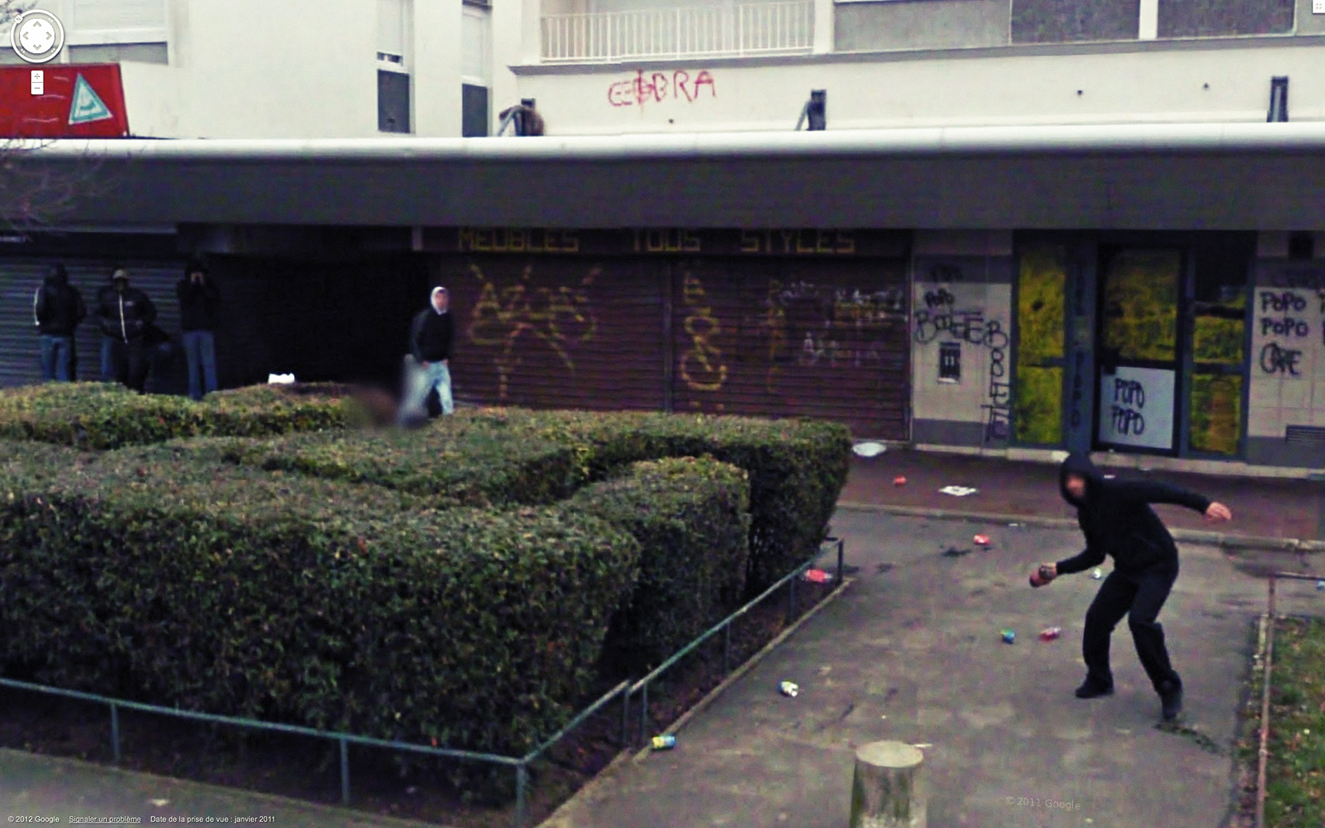 This colour photograph of an urban setting shows building façades covered in graffiti. A man dressed all in black, his face blurred, is preparing to throw something toward the camera.