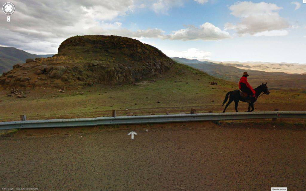 This colour photograph shows a vast mountainous landscape. A guardrail marks the edge of a road. On the far side of the guardrail is a man on horseback.