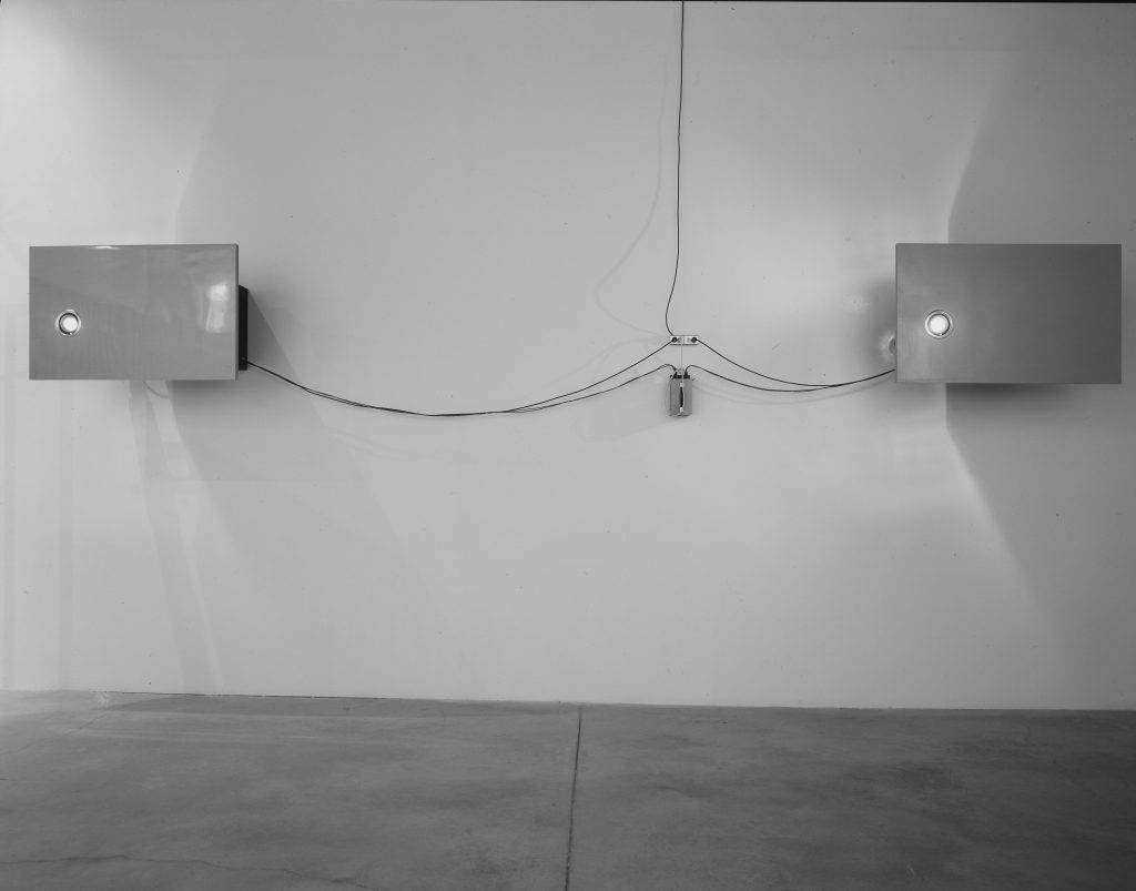 This photograph shows two white, rectangular projection devices attached to a white wall. They are connected together by electrical wires.