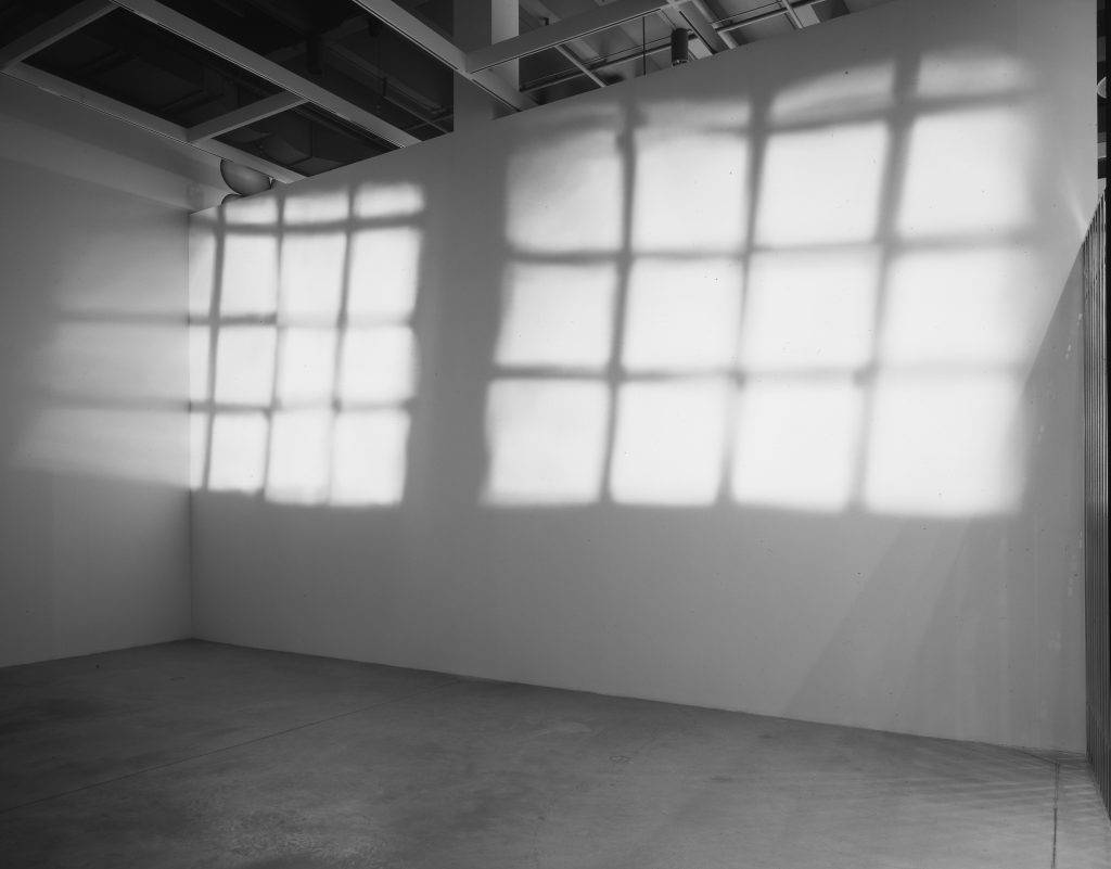 This photograph shows two white-painted walls of an empty room. Projected squares of light forming two grids illuminate the upper part of one wall.