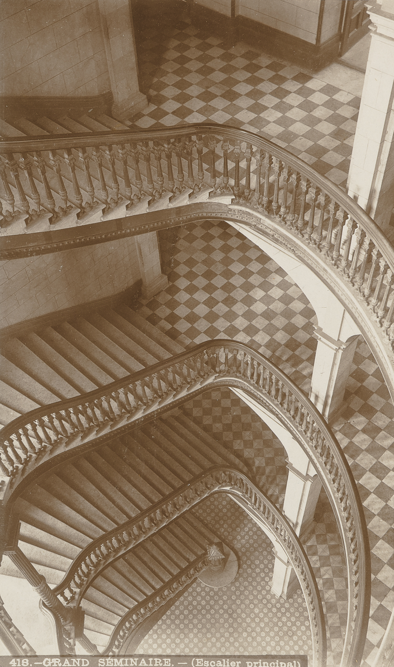 This photograph shows the four flights of a spiral staircase seen from the top. The landings have checkerboard-patterned floors. The structure is supported by stacked white columns seen on the right.