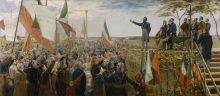 On the right side of this painting, a group of men is standing on a platform. One of them is addressing a large crowd, with one armed raised. Waving Patriote flags, the crowd occupies the left side of the composition.