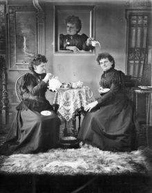 Two identical women are having tea in a Victorian decor. The one on the left is pouring, while the other looks toward the viewer. Behind them, a third identical woman is reaching out of a picture frame to pour cream on the head of the woman at the right.