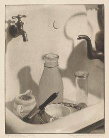 This photograph shows a porcelain kitchen sink in close-up. In the sink are a plate, a cup, a cream pitcher, a knife and two glass bottles. The spout of a metal teakettle at the right of the photo counterbalances the metal faucet in the upper left corner.