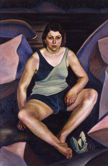 A woman in a tank top and shorts is sitting on the bank of a lake or river, facing forward. She is surrounded by violet and bluish rocks. Her knees are spread apart and her feet are crossed. A small plant is growing near her feet.