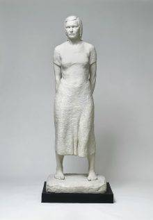 Linda is a white plaster statue of a woman standing with her bare feet firmly planted on the ground and her hands behind her back. She is wearing a simple dress and looking straight ahead with a determined expression.