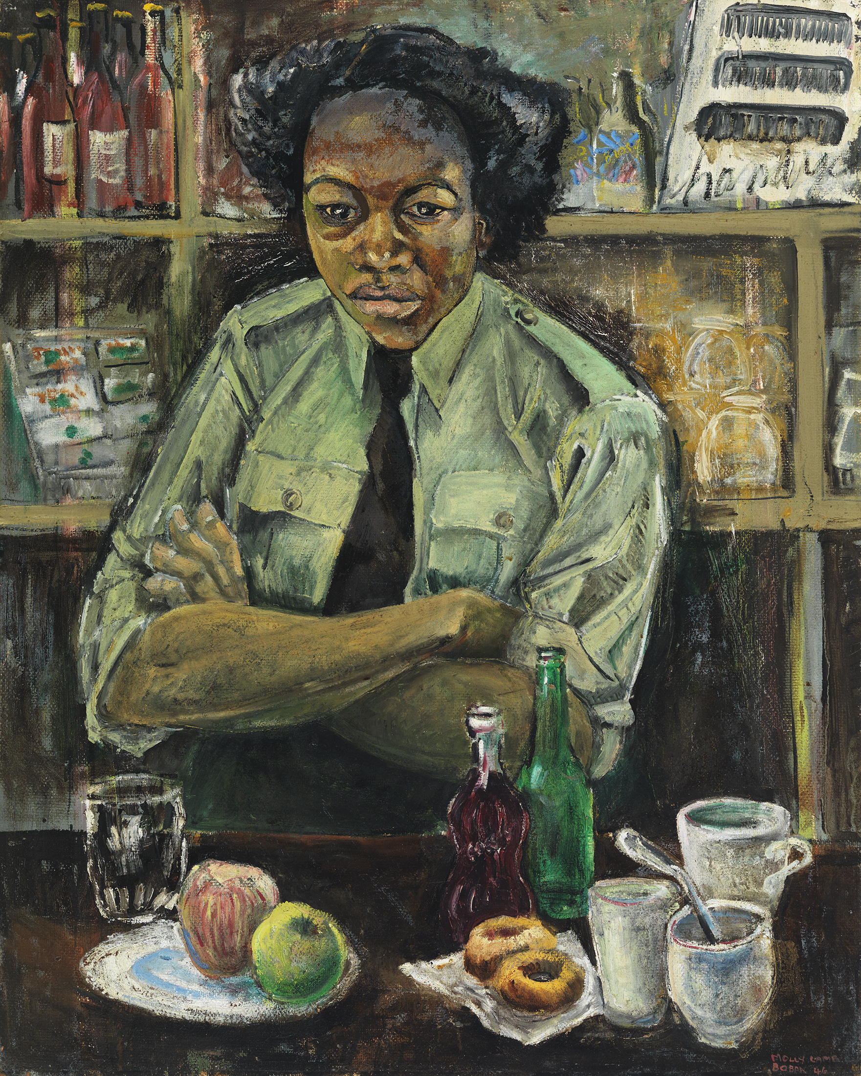 A black woman in a Canadian Army uniform is facing forward, her arms crossed. On the counter in front of her are two pieces of fruit, two doughnuts, bottles, cups and glasses. Behind her are canteen shelves stocked with provisions.
