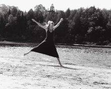 "In this black-and-white photograph, a dancer in a sleeveless dress is performing a choreography on a riverbank, barefoot in the sand. Her legs are spread and her arms are raised wide, making her body form an ""X."""