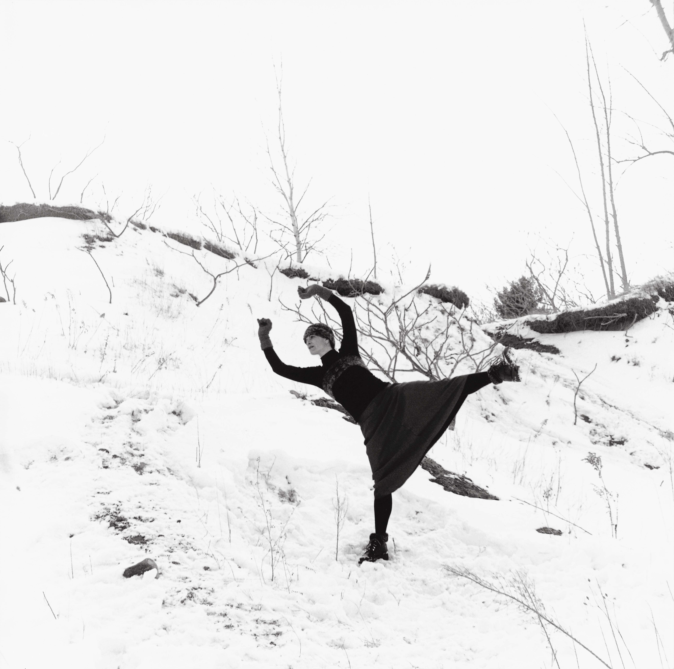 In a wintery landscape, a woman is performing a dance movement on the edge of a snow-covered mound. She is leaning forward with her knees bent and her arms raised behind her like the wings of a bird.