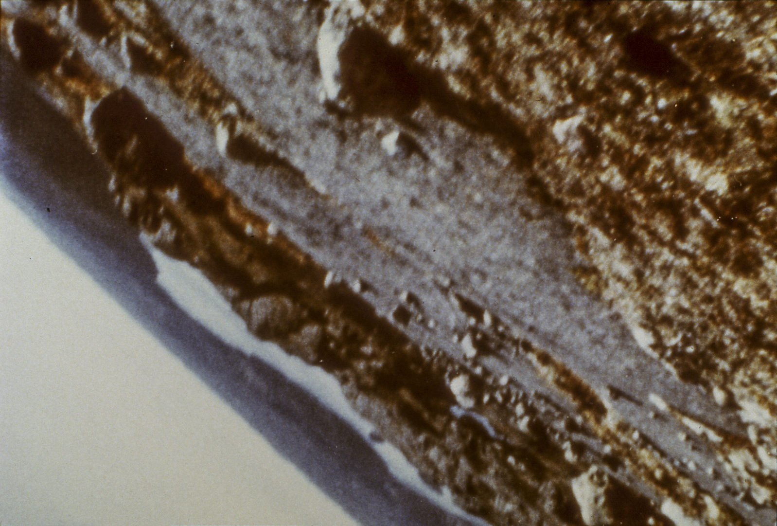 This image taken from the film shows a landscape tilted at a 145-degree angle. The horizon and a bit of clear sky are compressed into the bottom left corner. The rocky ground occupies most of the image.
