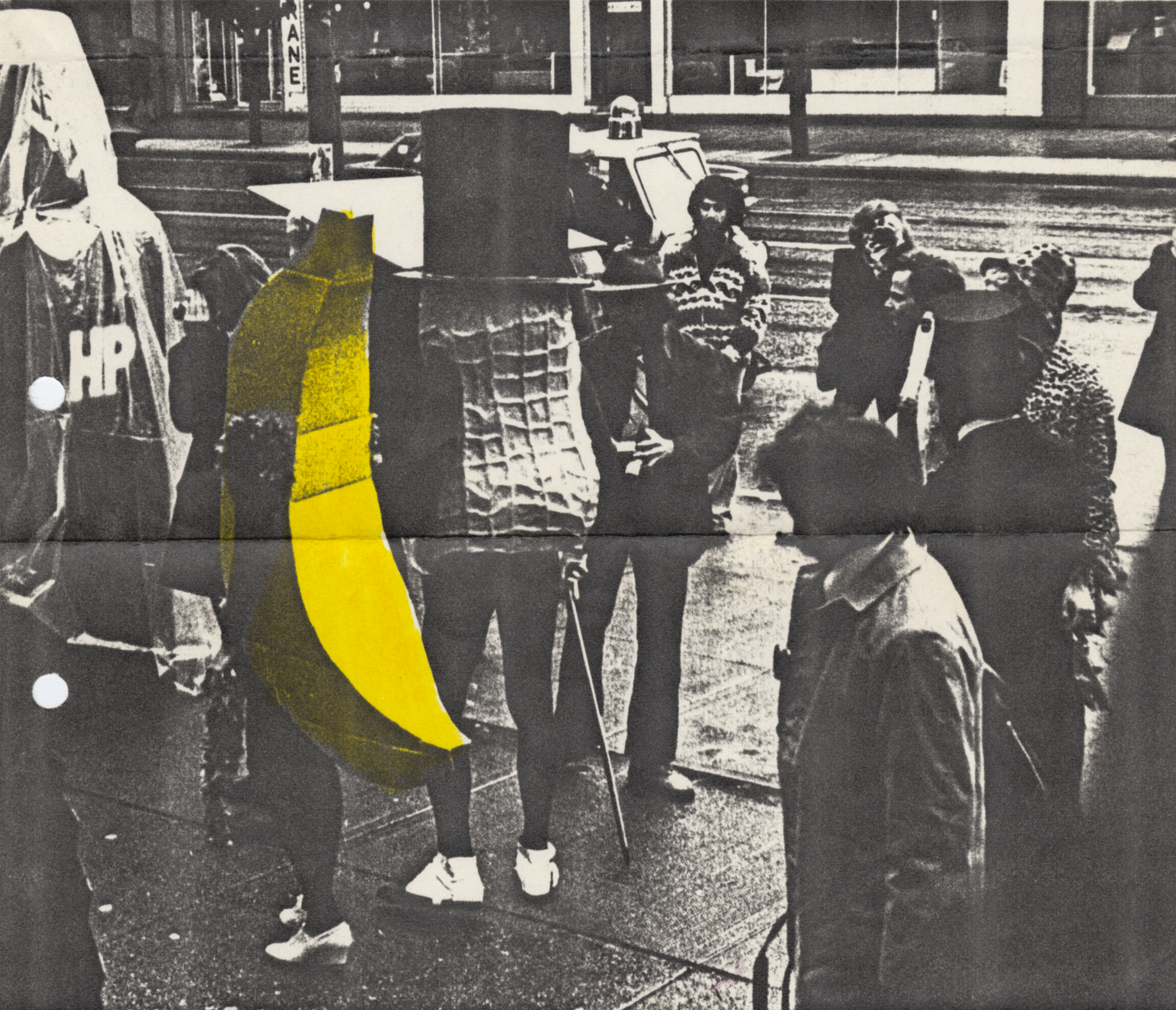 This black-and-white photograph shows a crowd of people around two costumed figures seen from the back. One is dressed as a banana and the other as a peanut.