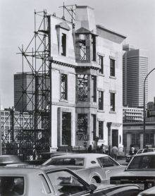 A black-and-white photograph shows a plywood façade seen from an angle. The structure is supported from behind by scaffolding. Cars are driving by in the foreground while skyscrapers appear in the background.