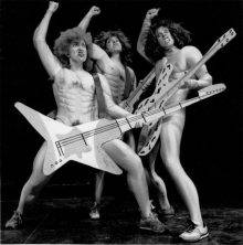 Three women wearing naked-muscle-man bodysuits and fright wigs are flaunting giant fake guitars. Standing spread-legged and pumping their right fists, they are imitating a rock band giving a show. Their faces are contorted in rebellious victory.