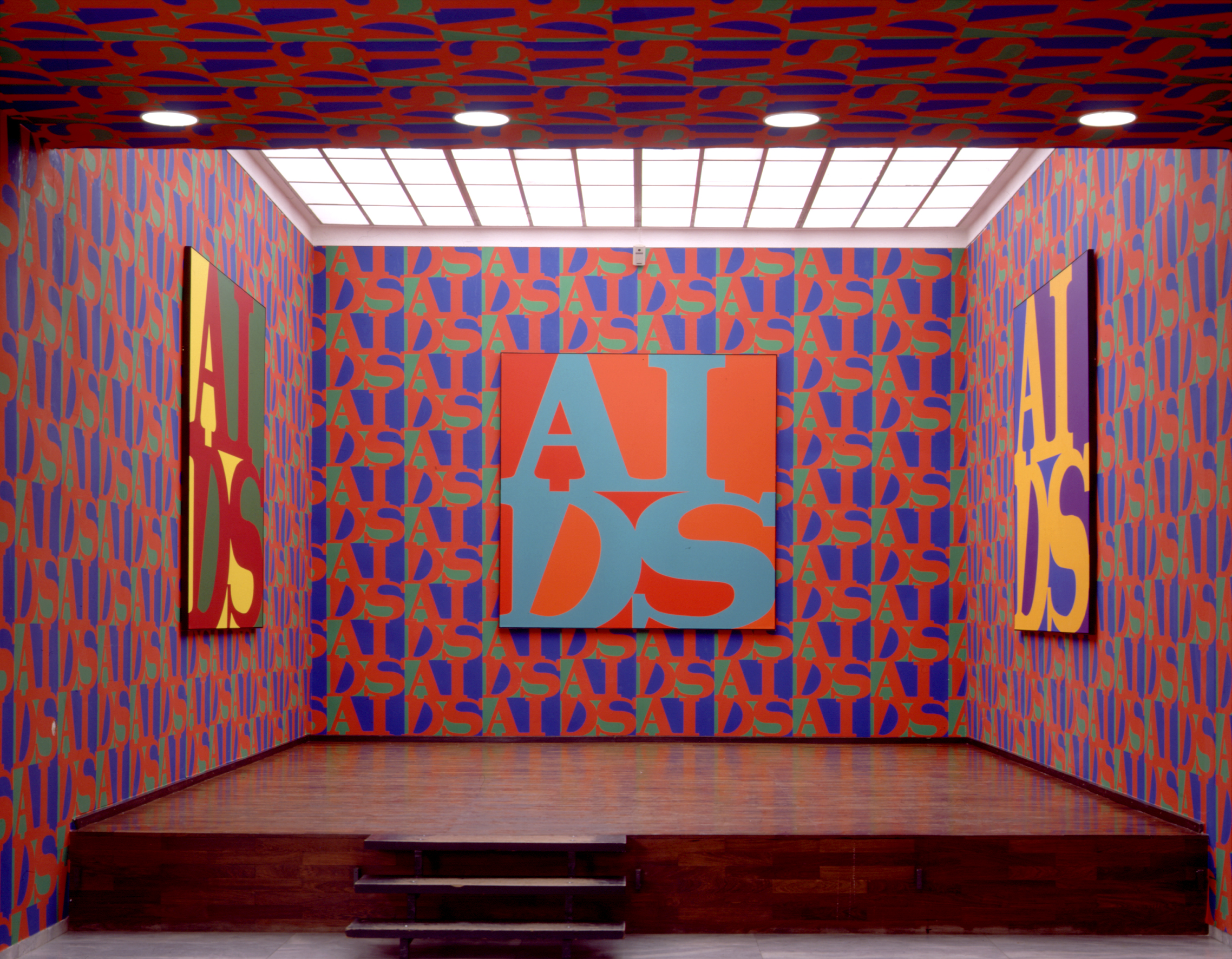 The word AIDS is painted in blue on a square red-orange canvas hanging on the back wall of a ceiling-lit room. On the left and right walls are two paintings of the word in other colours. Wallpaper with the same design in different colours covers the walls and part of the ceiling.