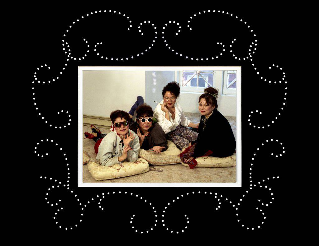 In this colour photograph, four women are lounging on cushions on the floor. Two are wearing sunglasses and one is smoking a cigarette. The photo is framed by a wide black border with a design of white dots.