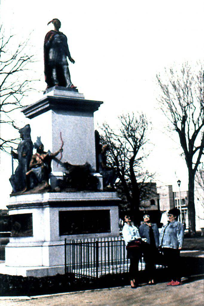 In this colour photo, three women are standing at the foot of a monmument dedicated to the Mohawk chief Thayendanegea (Joseph Brant) and the Six Nations Confederacy.