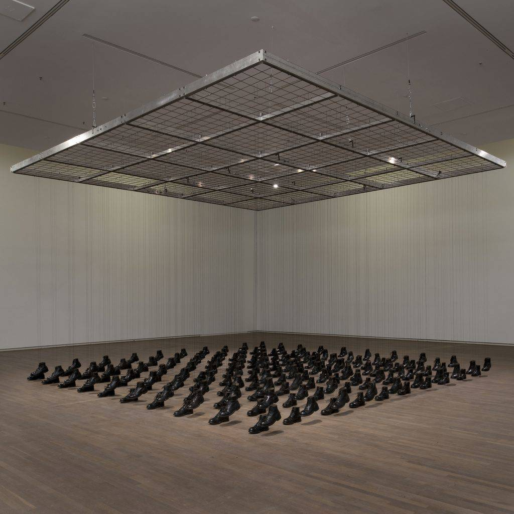 100 pairs of military boots arranged in ten rows of ten are suspended from a metal grid on black strings. The right-foot boots, raised slightly off the floor, create the impression of troops marching.
