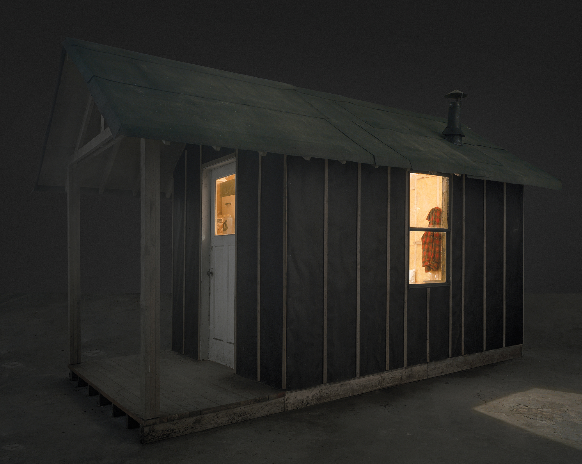 This photograph shows a wooden cabin with a pitched roof in a gallery space. Light is shining through a side window. On the porch there are two gasoline cans and some firewood.