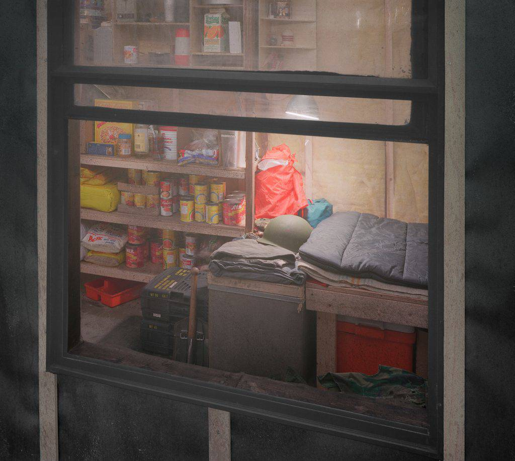 This photograph shows the inside of a cabin through a window. The various items in the small room include a bed, an army helmet, shelves stocked with non-perishable food, and clothing. The walls and ceiling are lined with fiberglass insulation.