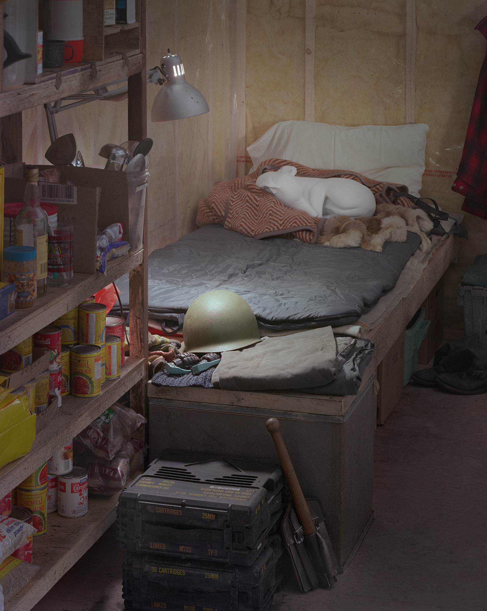 This photograph shows a bed with a pile of blankets, a cast figure of a dog and an army helmet. At the foot of the bed are shelves stocked with non-perishable items. The walls are lined with fiberglass insulation.