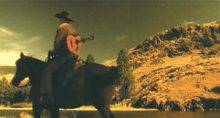 This low-angle image taken from a film shows a man, in three-quarter back view, riding a bay horse. He is wearing a cowboy hat and has a guitar slung across his back. In the background, rocky hills rise along a river.