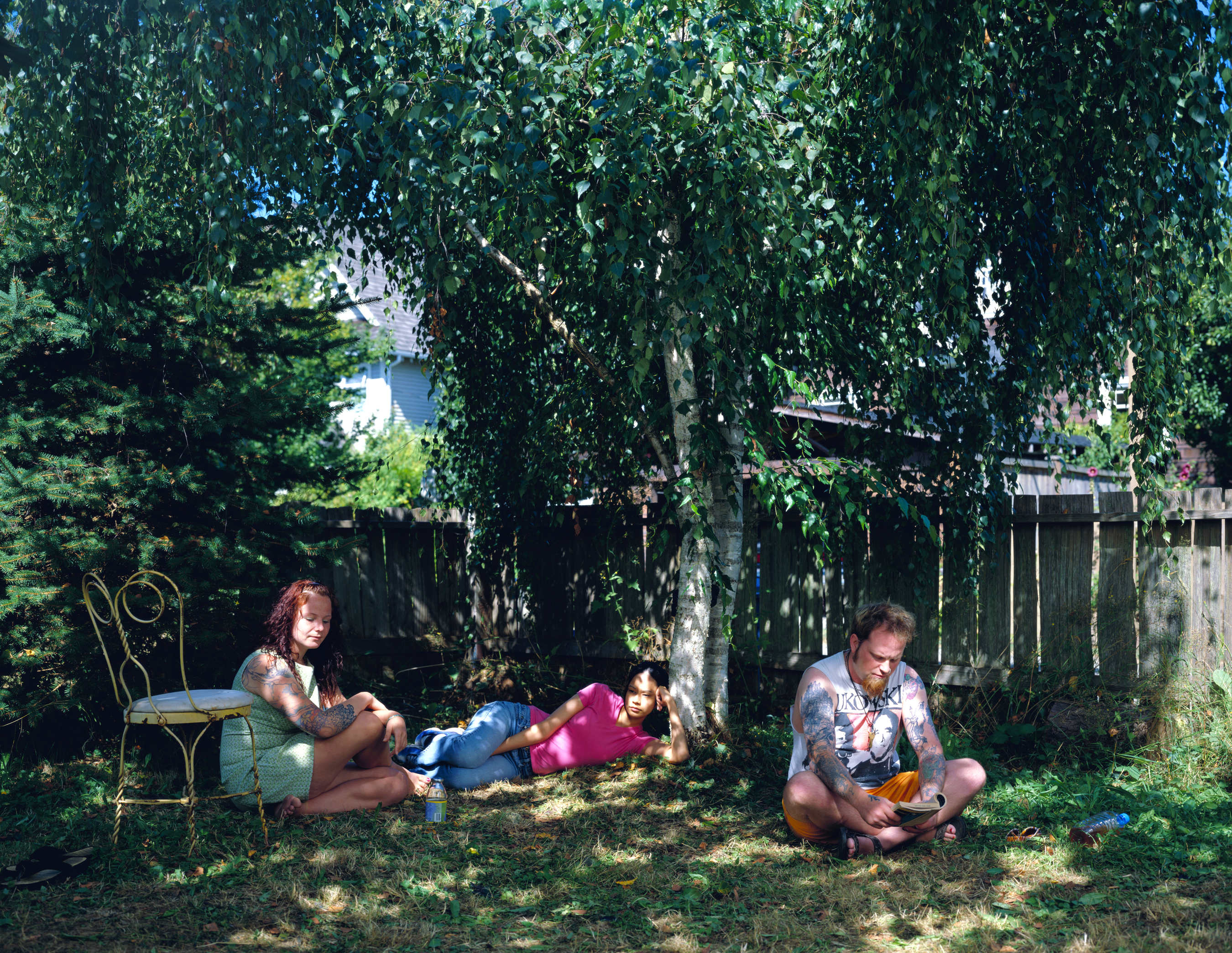 This colour photograph shows three people lounging under trees in a backyard. One woman is sitting on the ground near a chair, while another is lying in the grass. A man sitting apart from them is reading a book.