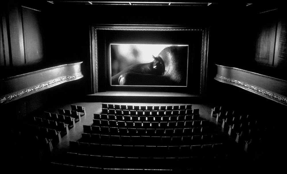 This black and white photo shows the inside of a movie theatre where a film is projected. The close-up of a face appears on the screen.