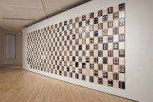 This work is composed of 426 small painting mounted on a wall in a way that suggests a series of woven placemats. On each painting are handwritten words overlaid with spots and checkered motifs in varied light and dark shades.