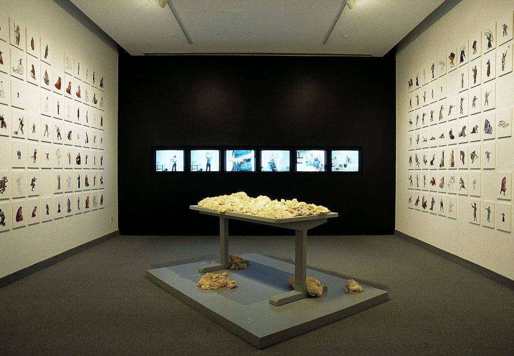 In this installation, about 250 images are hung on the side walls of a gallery, and six video monitors are set in the back wall. At the centre of the space, a table heaped with salt dough stands on a low platform.