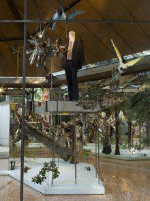 In this photo, a low platform holds an assemblage of metal objects, taxidermy animals and artificial plants. A male mannequin dressed in a suit stands on a raised platform. Its head has been replaced by a cast rooster head.