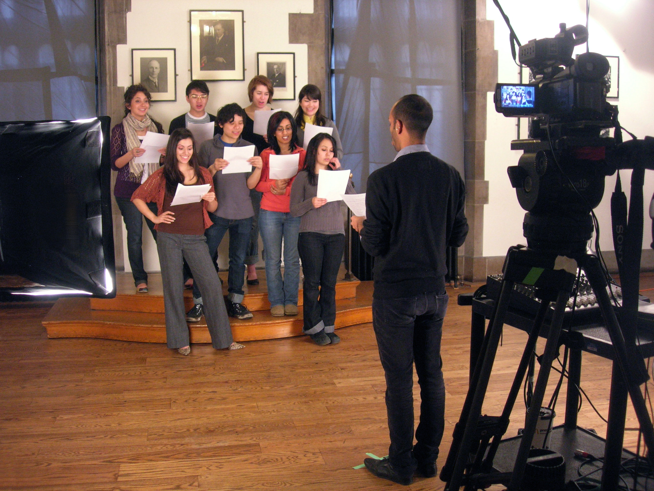 Eight people are standing in two rows. Each one is holding a sheet of paper. A man seen from the back is directing the group. Behind him is a camera.