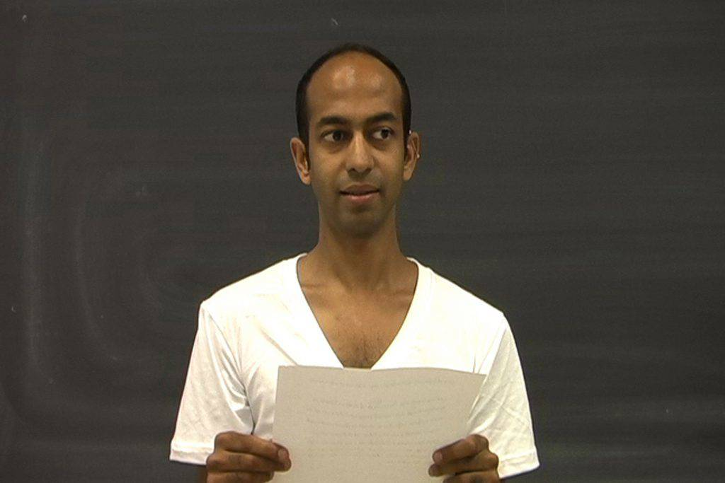 This image taken from the video shows a man, bust-length, holding a sheet of paper. He is wearing a white T-shirt that contrasts with the dark grey background.