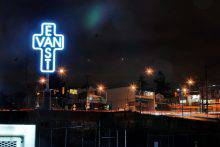 """This photograph shows an immense illuminated sculpture in the shape of a cross rising above an urban landscape. Within the cross, the vertical word """"East"""" and the horizontal word """"Van"""" intersect at the letter """"A."""""""